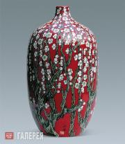 Vase with decoration of flowers of white plum against a red background