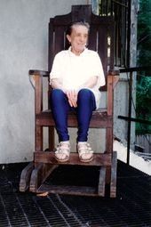 Louise Bourgeois at home in 1995 sitting in the electric chair later used in Passage Dangereux (1997). Photo: © The Easton Foundation