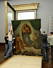 Gallery assistants lift the Sistine Madonna to hang it in its new hand-crafted frame at Dresden's Galerie Alte Meister Museum, May 23 2012