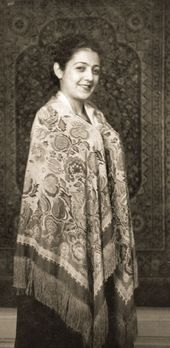 Zoya Kalatozova in a shawl with a carpet in the background. 1948
